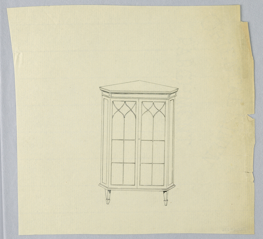 Triangular corner cabinet with canted corners and 2 glass door front panels with Gothic-inspired tracery; raised on 3 (2 shown) short tapering legs.