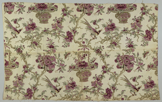 Polychrome block print in purples and greens on natural linen. Elaborate containers of flowers are suspended from branches of serpentine branches which have birds perched on them, purple flowers and fruits. Pattern repeats side to side.