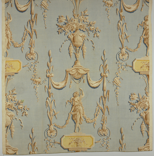 Block printed linen in shades of tan and yellow on a grey-blue background. Classical motifs: a half-draped female figure, in shades of tan, holds swagging floral garlands, stands on an elongated octagonal plaque-yellow, with basked of tan flowers in center. Figure stands under a draped canopy with tassels, supported by plant stalks. On top of canopy a large tan urn containing tan flowers. Vertical repeat of pattern incomplete. Pattern half-drop repeats on either side of central repeat, when matched side to side. Condition: soiled