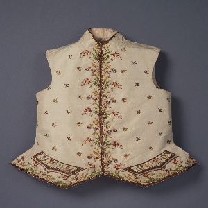 Embroidered wasitcoat with floral design continuous at the front and lower edges and pocket area, with small offset sprigs spaced over the ground. Small standing collar.