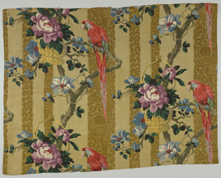 Polychrome block print on linen. Visually, two layers of patterning. Background light tan-gold with three darker tan stripes patterned alternately by scrolling vine in brown; Greek key in brown or abstract flower and vine in brown. Top layer - serpentine branch with large blue flower supports, large red parrot and hanging yellow basket with a large lavender flower and green leaves. Pattern repeat - half drop. Condition: soiled