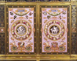 Upright cabinet made of porcelain plaques in a gilt-bronze armature, of two sections; the upper section with two large doors and a peacock crest, the lower section projecting forward with a glass top, supported on two ceramic columns, and containing two drawers.  The porcelain plaques painted with allegorical and naturalistic ornament, featuring two large roundels on the doors with cameo-like images of Psyche (left) and Venus (right).  Bronzework and porcelain ornamented throughout with neoclassical motifs including swags, volute scrolls, grotesques, and palmettes.