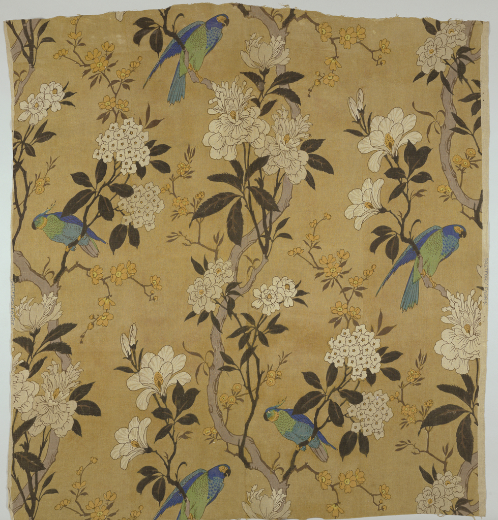 Polychrome block print on tan linen. Pairs of green and blue parrots perch on the branches of a flowering tree with clusters of both white and yellow flowers.