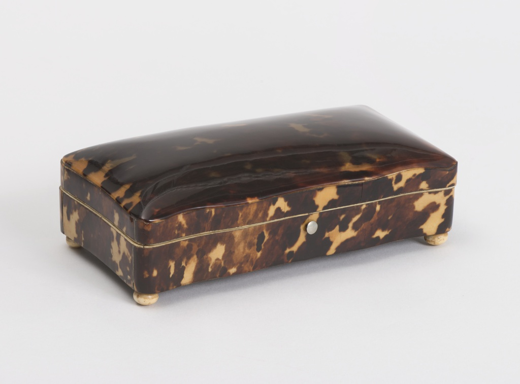 Rectangular box of wood with wavy sides and hinged cover. Sides covered with flamy tortoise-shell; top cover is domed sheet of tortoise-shell without backing. Inside edges lined with strips of ivory, the box itself with dark purple velvet. Four ivory ball feet.