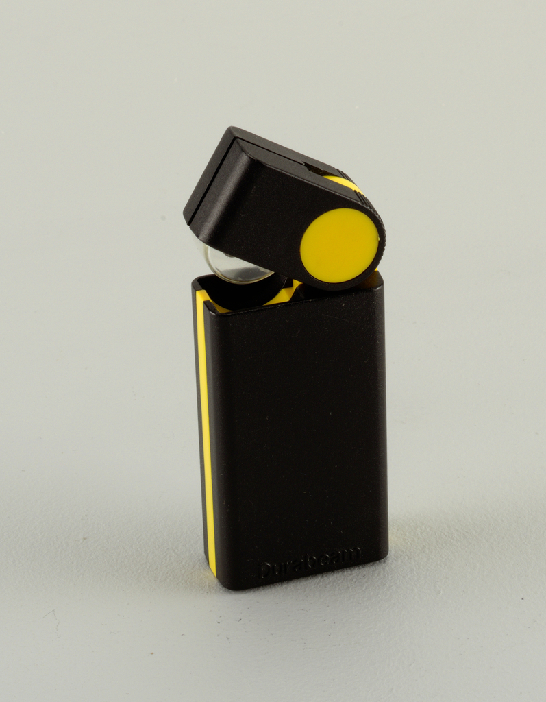 """""""Cigarette lighter""""-like rectangular black body with yellow stripe, yellow disk at joint with pivoting rectangular head; small lamp contained in head."""