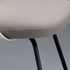 Upholstered side chair on four black steel legs; square seat with curved corners, covered in light brown nylon and wool; arched back, upholstered in cream colored vinyl, wraps around sides of seat.