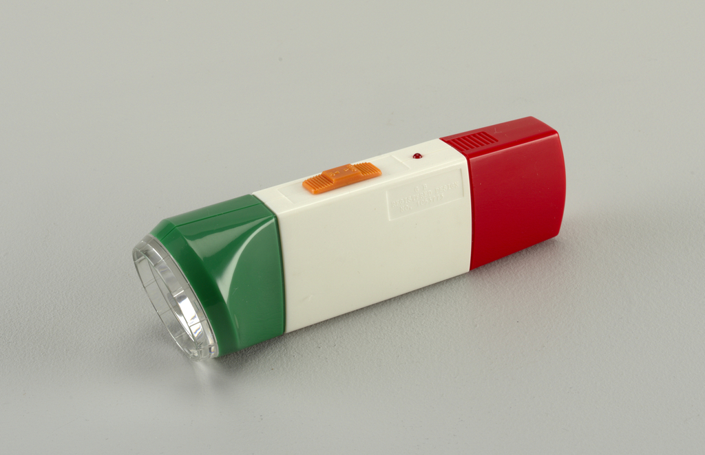 "Green white and red molded plastic housing of flat rectangular form flaring at one end into circular lamp housing; orange rectangular switch with ""on/char"" molded in surface."