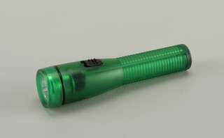Translucent matt-textured green body consisting of circular top (a) with light bulb and clear lens, mounted on cylindrical shaft tapering into a ribbed handle (b).  Black on/off switch on shaft.