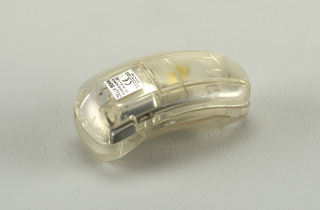 "Bean-shaped translucent clear body (a) with interior spring-operated opening/closing mechanism; grey ""open"" button at top right.  When button pressed, cover slides down to reveal lens and light bulb. Rectangular battery compartment cover (b) on back."