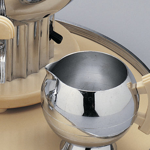 Sphere shaped chrome coffee maker with a small nozzle on the lower front and a chrome lid with a clear knob.  Coffee maker sits on a scalloped chrome cylindrical base and also has two cream colored handles plastic handles on opposite sides.