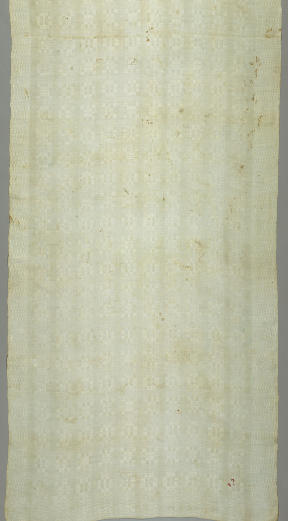 """Natural linen cover with a continuous pattern of squares and rectangles arranged in stripes with small closely set rectangles for side borders. Initials """"D.J. 7"""" embroidered in red linen on one corner."""