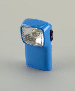 Upright blue, rectangular form, horizontal retangular lense and bulb housing at top, facing forward; black sliding on/off switch on right side.  Body opens in clam-shell manner, hinged on one side.