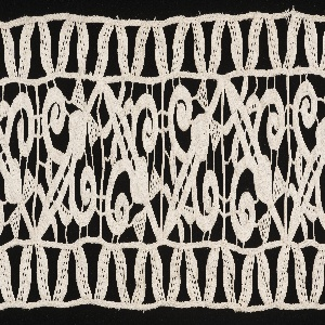 Border of square compartments filled with repeated floral form and edged with narrow border of zigzag design at either side.