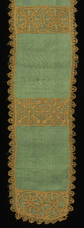 Narrow panel of green moiré silk trimmed along all edges with a narrow border of ecru lace. Narrow bands of ecru lace also lay across green silk in intervals forming bands. Bands have geometric wheel patterns.