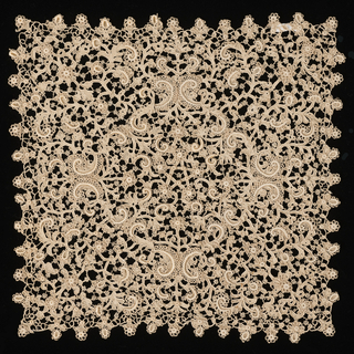 Square with scrolls radiating from a central star-shaped motif. Scrolls and flowers decorated with padded and raised details. Pattern areas connected by brides with wheels.