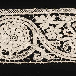 Design of stem with scrolls surrounding flowers.