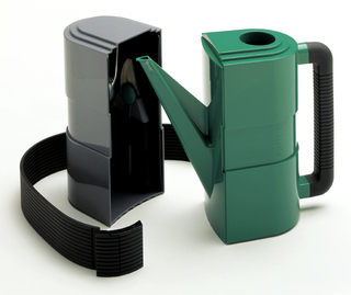 A black plastic tool case, having a rectangle shape with rounded corners on half the object. Opening on the side, the tool case is hollow and includes a black band with horizontal stripes. A matching watering can fits into this piece as a set.
