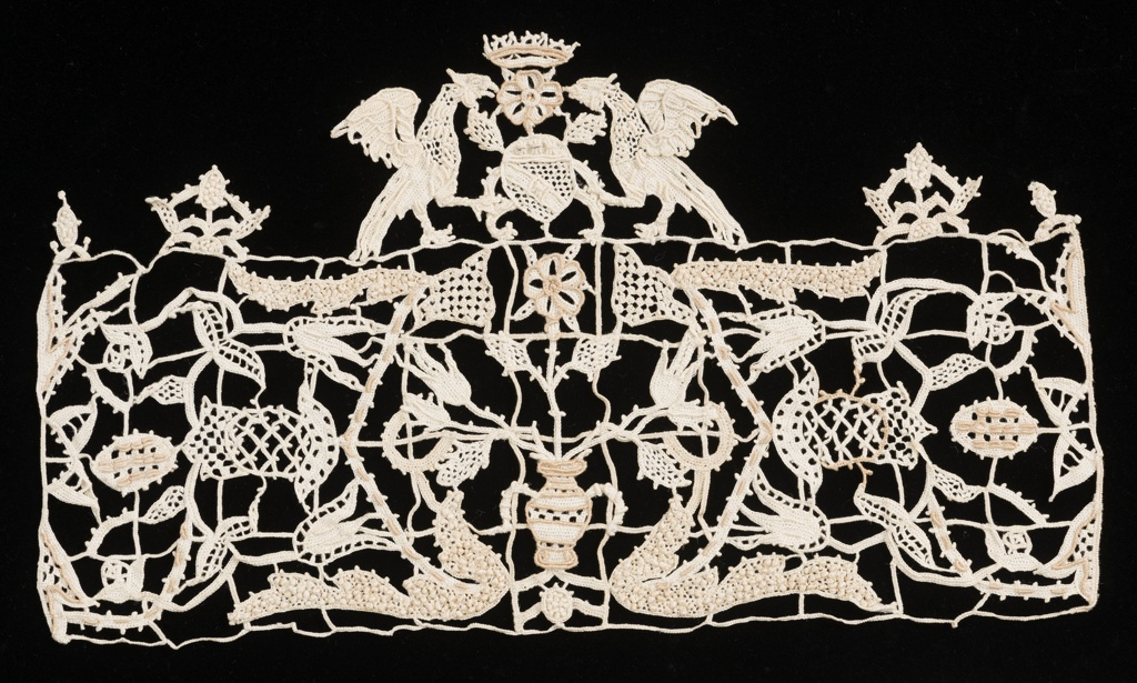 Border fragment by Aemilia Ars with four rows of small scale squares filled with floral forms and surmounted by crest of two confronted eagles.