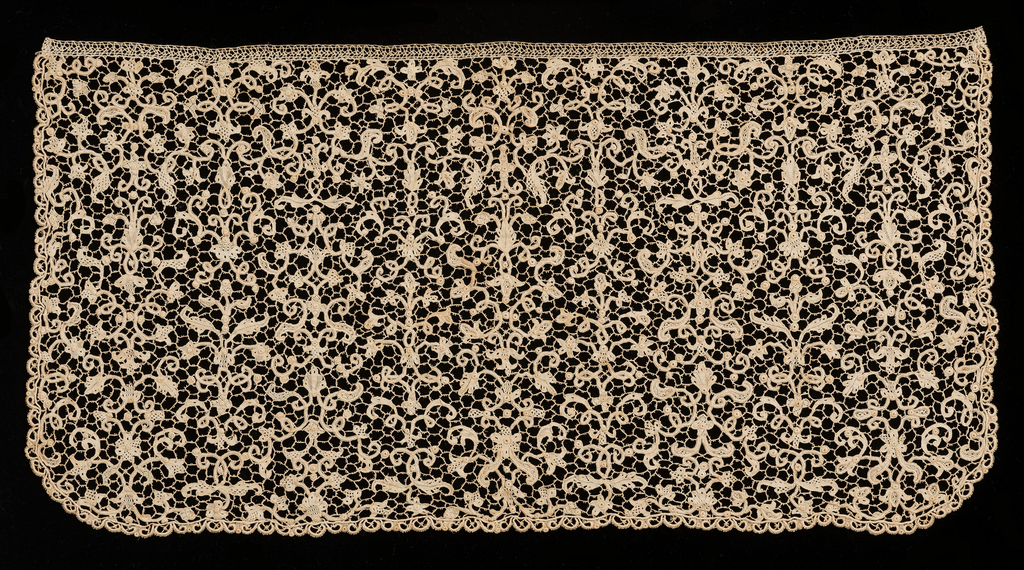 Cravat end showing a design of scrolling flower and leaf forms arranged in a candelabra pattern. Edged on three with narrow scallops of needle lace.