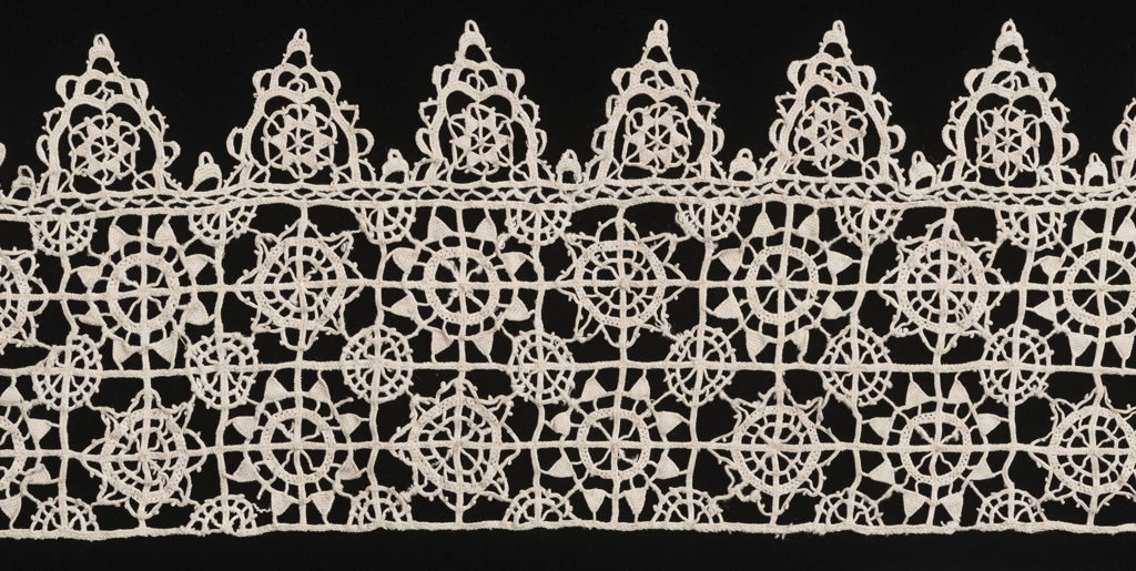 Wide border of two rows of squares bordered at one side by pendants. Squares and pendants filled by circular blossoms.
