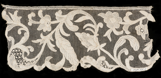 Part of a border from with a design of a scrolling stem with leaves, flowers and fillings.