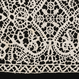 Lace border with quatrefoil motif combined with balanced scrolls and narrow pointed edge. Bobbin heading.