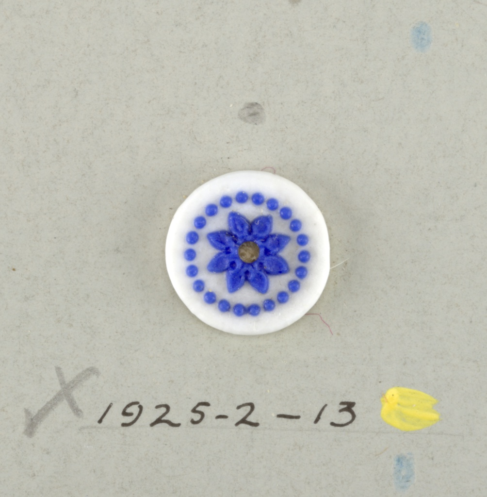 Circular medallion in the style of Wedgewood Jasperware; showing open flower with eight petals surrounded by ring of dots; blue on white ground. Central hole.  On card 4