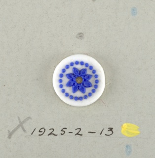 Circular medallion in the style of Wedgewood Jasperware; showing open flower with eight petals surrounded by ring of dots; blue on white ground. Central hole.