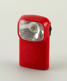 Upright  red, rectangular form, horizontal rectangular lense and bulb housing at top, facing forward; black sliding on/off switch on right side.  Body opens in clam-shell manor, hinged on one side.