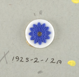 Two circular medallions in the style of Wedgwood Jasperware; each showing a flower with twelve pedals; blue on white ground; central hole.