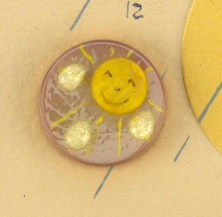 "Eighteen buttons on a sheet with a smiling and winking sun. The buttons are in various colors; each has a sun with a smile and beads in raindrop shape. Buttons are placed in form of raindrops progressively getting larger below. Board titled in blue: ""La Mode Presents… / April Showers / DESIGNED BY Marion Weeber""."