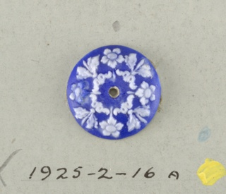 Circular medallion in the style of Wedgwood Jasperware; showing four open flowers alternating with four leaf ornaments with scrolls and dots; white on pale blue ground; central hole.  On card 4