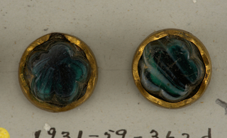 all buttons of glass made in imitation of malachite - a/: circular, flat button pierced in center with brass ornament on shank - b,c,g/: oval buttons made of stone set in scalloped brass collets - d,e,f/: circular stones set in scalloped brass collets.  On card 17