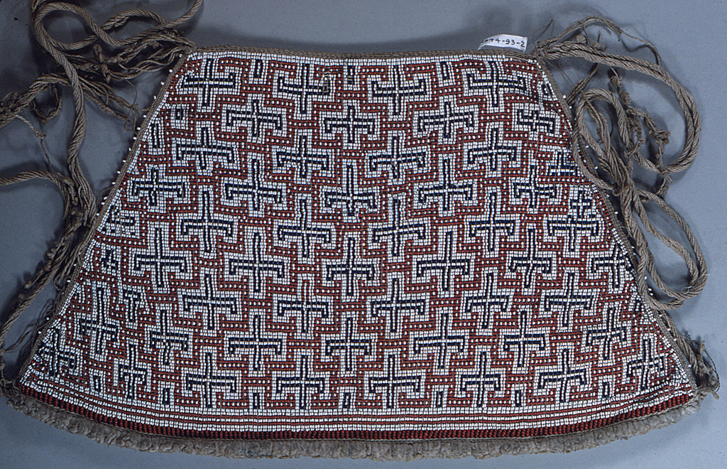Woven beadwork in design of crosses in blue with surrounding lines in red on a white ground. Cotton strings for tying and for ornament. Border at the bottom of wool (?).