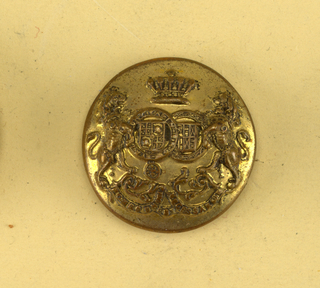 "Convex button showing coat of arms; two sheilds with heraldic devices surrounded by chains, lions supporters crown above and below, ribbon with ""Porro unum est necessitarium"". Brass back and shank. On reverse, ""Firmin and Sons, 153 Strand London"".  On card C"