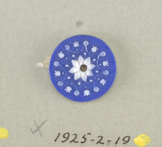 Circular medallion in the style of Wedgwood Jasperware; open flower with eight petals in eight pointed star, with dots and ornaments; white on blue ground, central hole.  On card 4