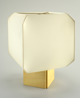 Table lamp on a square, natural wood base with four-sided white plastic shade supported by brass wires.