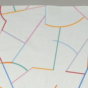 Length of printed cotton with brightly colored angular and curving lines on a white ground.