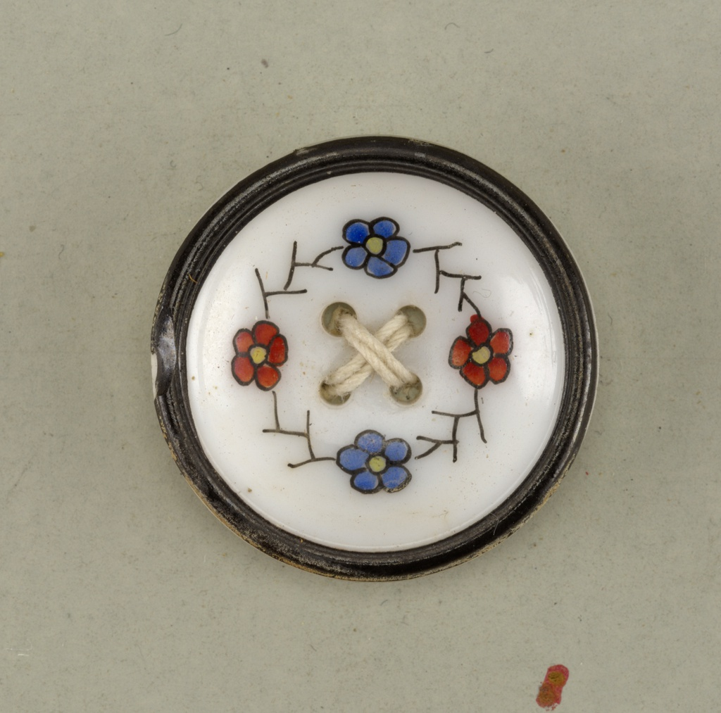 concave button ornamented with four small flowers [two red and two blue]; four holes.