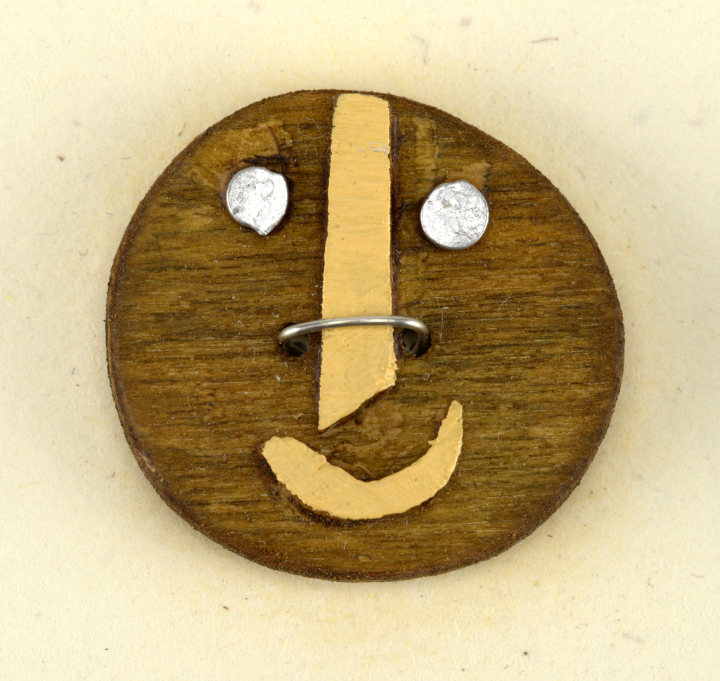 """Circular """"face"""" of dark wood with applied metal eyes, and nose and mouth of painted wood."""