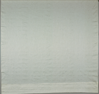White fabric with a sheer design of leaves against the light. The fabric is puckered.