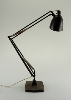 Black enameled lamp surmounting flexible arm with four springs, on square metal base with short neck.