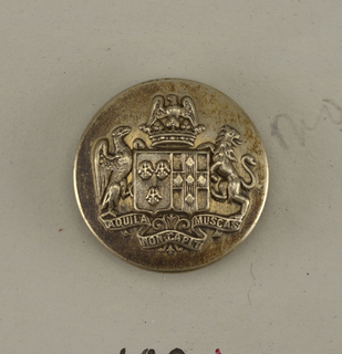"Circular, slightly convex button with ornament showing a shield with heraldic devices, eagle and lion supporters, a crown above and below, ribbon with ""Aquila non capit Muscas"". Brass back and shank. On reverse: ""C T paris"". ""Perfectionne"" on belt with buckle.  On card E"