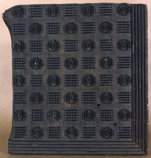 Part of a design for a table cloth with squares formed by dots and a rose alternating. A border of five flat metal strips.