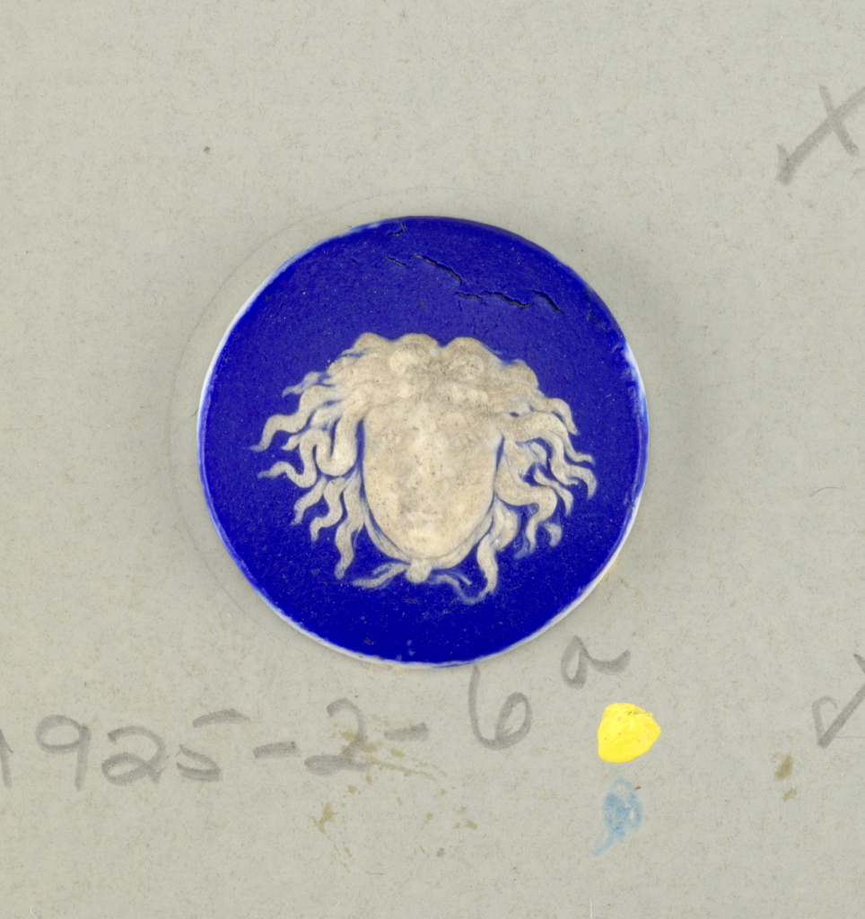 Medallion or mount in the style of Wedgwood Jasperware; ornamented with Medusa head shown full face; white on a blue ground.