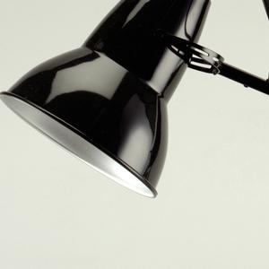 Black enameled lamp surmounting flexible arm on stepped square base; three springs near base.