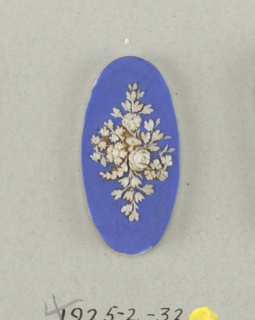 Oval medallion in the style of Wedgwood Jasperware; ornamented with flowers and leaves; white on blue ground.  On card 4
