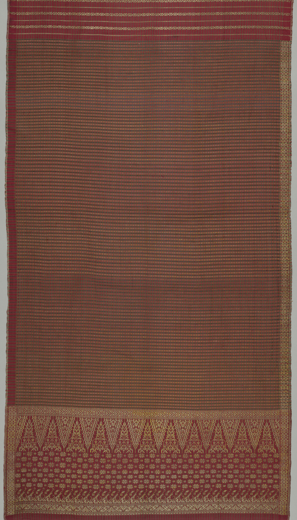 """Long narrow panel in three sections. In the largest section, the field is patterned by a small scale plaid in red, black, and yellow with the addition of a small scale pattern or narrow bands. At one end there is a deep border patterned by narrow isolated gold bands on a red and black striped ground. At the opposite end, there is a more elaborately patterned border in gold on a red and black striped ground featuring the """"tumpal"""" motif (row of isosceles triangles). A narrow geometric band in gold is continuous along what would be the bottom of the sarong when worn."""