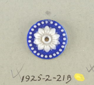 Three circular medallions in the style of Wedgewood Jasperware; open flower with twelve petals surrounded by ring of dots; white on blue ground; central hole.