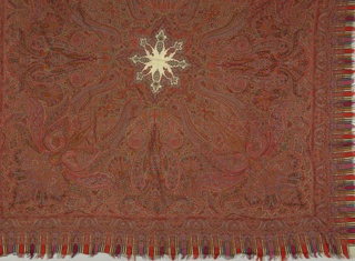 Predominantly red shawl with a white star shape in the center.